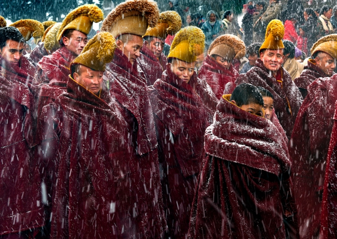 My image refers to a particular circumstance in which the Buddhist monks were walking to the Buddhist Rite(Ceremony) in the heavy snow. It took place in Langmu Temple of China on March 4th(the 15th of the first lunar month), 2015. Langmusi is not just a temple, the small town itself, half of which is in Gansu Province and half in Sichuan Province. Half of the people here are Tibetans and half are Muslims. Buddhist Tangka, Shaidafo is a routine Buddhist ceremony which is held on this day every year.