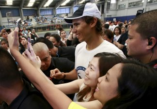 Fans of tennis player Rafael Nadal take a selfie with him after a sports clinic hosted by Nadal at the Colegio De San Agustin in Makati city, metro Manila December 6, 2015. REUTERS/Romeo Ranoco