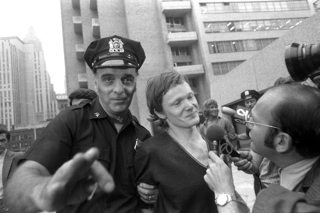 Philippe Petit (center) answers reporter's questions as he i